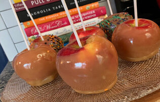 Caramel apples sitting on a glass tray in front of a stack of books