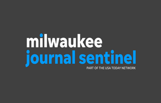 """Milwaukee journal sentinel"" written in white and blue block font on a charcoal grey background"
