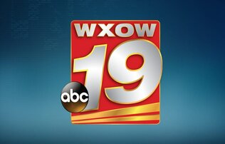 """WXOW 19"" written in silver lettering on a red and yellow rectangle. At the lower left just touching the rectangle there is a black circle that inside says ""abc"" in white font. All of this sits on a blue Ombre background."