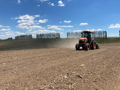 Red tractor seeding pollinator habitat with trees and blue sky in the background